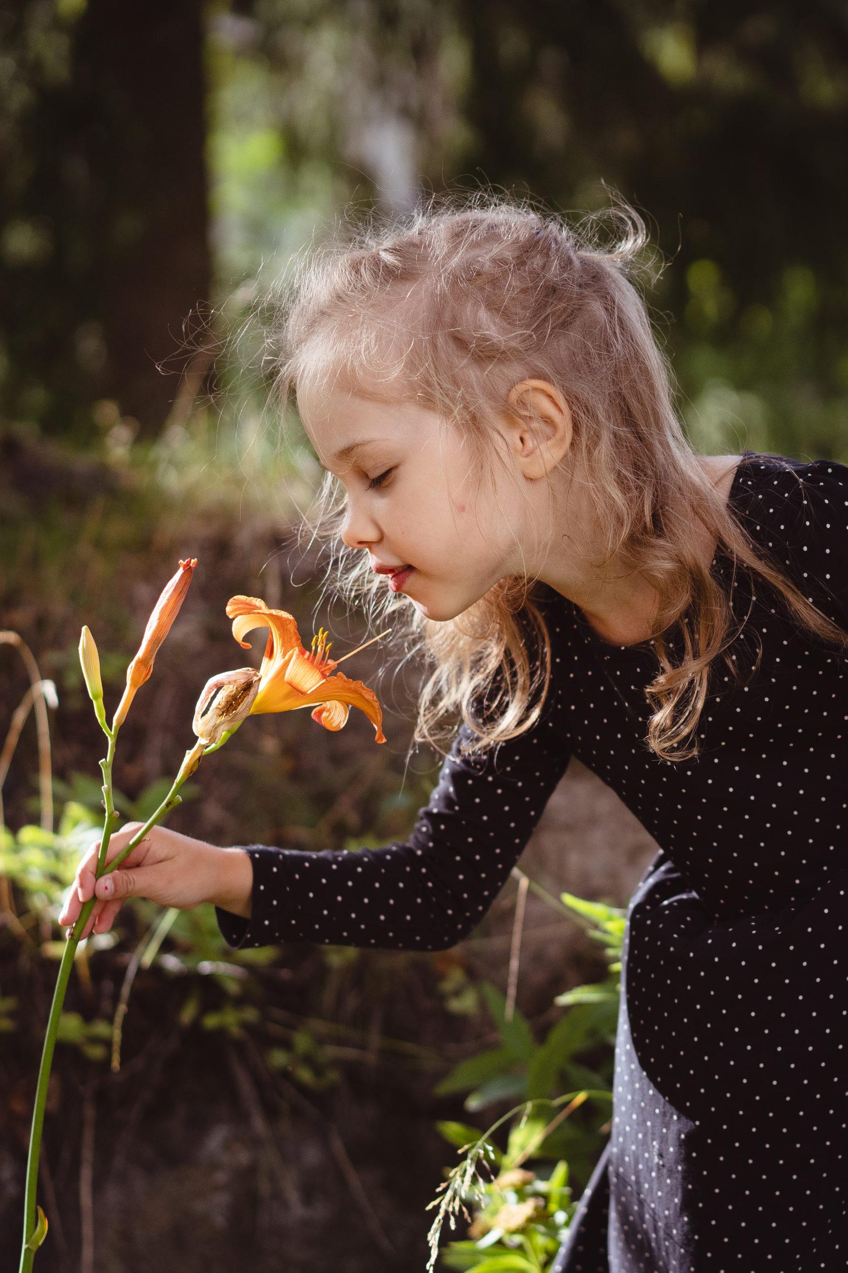 Muotokuva pienestä tytöstä, joka nuuhkii oranssia liljan kukkaa puutarhassa.